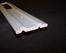 a custom foam thermoplastic extrusion with small circular holes, ridges, and a large rectangular hole